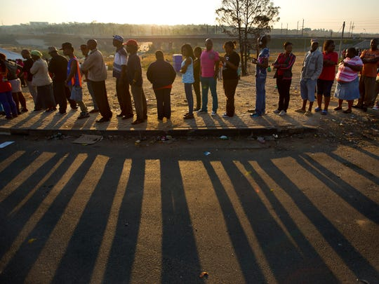 South Africans queue to cast their votes at sunset at a polling station in the Alexandra township of Johannesburg, South Africa.