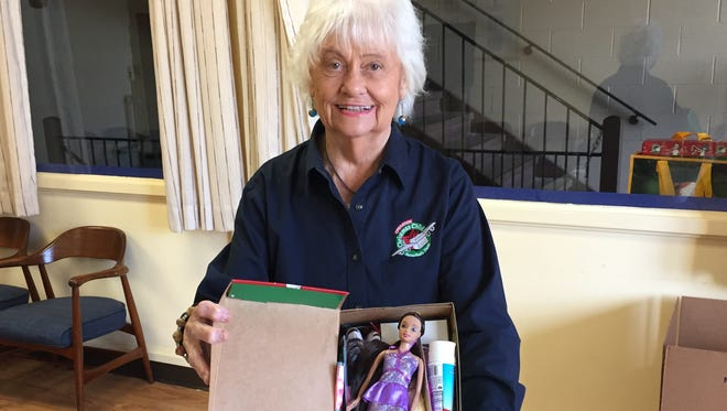 Peg Beukema displays a shoe box packed for a young girl for Operation Christmas Child.