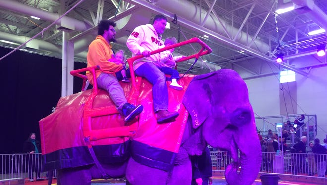 Audience members take a ride on a circus elephant prior to the Tripoli Shrine Circus at the Washington County Fair Park & Conference Center in West Bend on Tuesday night.