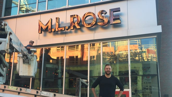 M.L. Rose's owner Austin Ray stands in front of the new restaurant space as a worker finishes installing the signage at Capitol View.