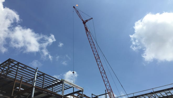 A crane lifts a steel beam signed by city, state and education officials into place at the Joint Health and Sciences Center.