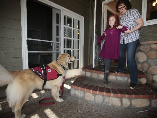 Alyssa Howes, 11, walks down the steps at her family's Lakewood, Calif., home with a little help from grandmother Cindy May and service dog Flint.