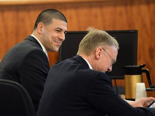 Former New England Patriots football player Aaron Hernandez smiles with defense attorney Charles Rankin in the courtroom of the Bristol County Superior Court House in Fall River, Mass., Wednesday, April 8, 2015. The fate of Hernandez is now in the hands of a jury, which began its first full day of deliberations Wednesday in his murder trial. Hernandez is charged with the June 2013 shooting death of Odin Lloyd.