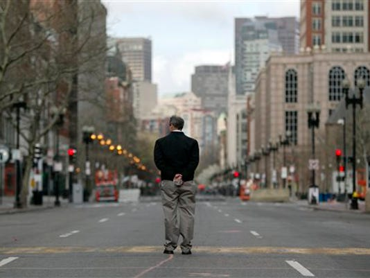 Jack Fleming, of the Boston Athletic Association, which runs the Boston Marathon, pauses at the finish line on Boylston Street between Dartmouth and Exeter Streets in Boston. Federal investigators formally released the finish line bombing crime scene to the city of Boston Monday in a brief ceremony at 5 p.m. (AP Photo/Robert F. Bukaty)
