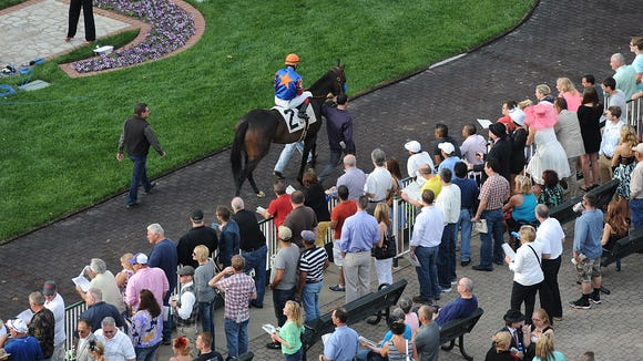 Race fans watch as the horses parade around the paddock at opening day of Churchill Downs on Saturday. April 26, 2014