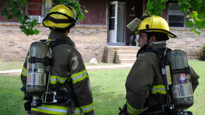Mountain Home firefighters discuss a smoke alarm call at 1115 Meadowcrest Drive Tuesday. Firefighters put out a small garbage fire inside the home after an alarm company alerted them to the fire.