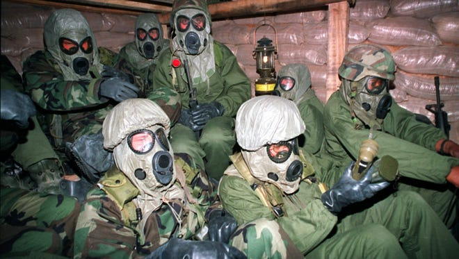 Soldiers with the Army's 7th Corps huddle in a bunker in eastern Saudi Arabia with gas masks and chemical suits just after U.S. planes started bombing Iraq on Jan. 18, 1991.  U.S. troops wore the protective outfits during the 1991 Persian Gulf War because of concern that Saddam Hussein might arm Scud missiles with dangerous agents from his chemical weapons stash.