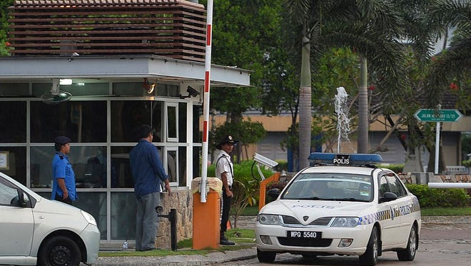 A police car passes the main gate of the house of missing Malaysia Airlines pilot Zaharie Ahmad Shah outside Kuala Lumpur on Saturday.