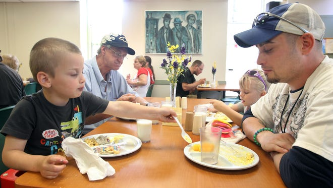 Braylon Dixon, 4, scoops pineapple pieces from the plate of his father, Dennis Dixon, as they have lunch at the Parish Kitchen.