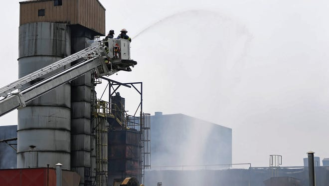 Firefighters spray water while working on the scene of a fire at Donsco Inc. in Wrightsville on Friday.