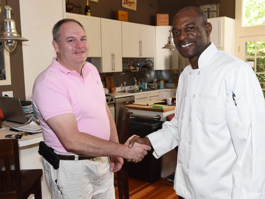 Rodrick Boney, right, shakes hands with Charles Fells, left, in Fells' Hyde Park home. Boney and his family are being provided with a room in Fells' home while Mr. Boney works as a sous-chef in one of Fells' restaurants.