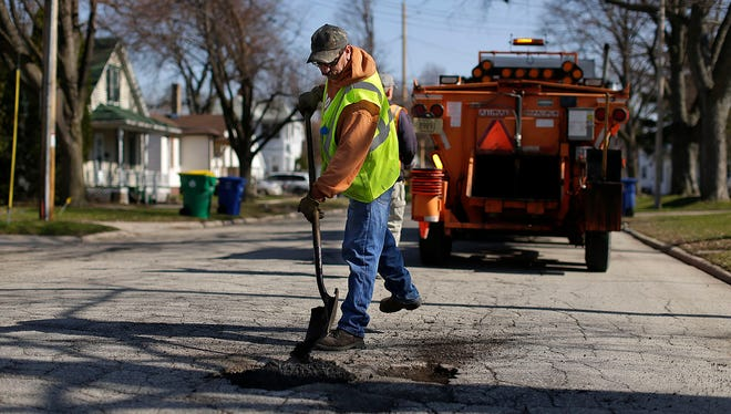 Ray Magley, with the Green Bay Department of Public Works, patches potholes along Roosevelt Street in Green Bay. One-third of Green Bay's roads are rated in poor condition.