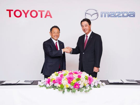 Toyota CEO Akio Toyoda and Mazda CEO Masamichi Kogai celebrate a partnership between their companies to develop electric vehicles and self-driving cars and build a $1.6 billion U.S. plant.