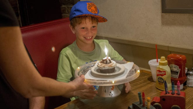 Tyler Mollman, 9, of Urbandale, receives his birthday cupcake after dinner at Maxie's Restaurant in West Des Moines this summer. Maxie's has two specials for dining out with kids. All day Mondays kids eat for $1. Kids eat free all day on Saturdays.