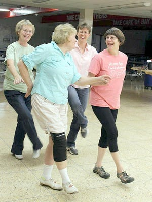 Lake Country Cloggers from left: Kathie Van Voorhis, of Webster; Mae Church, of Ontario; and Polly Mayne, of Canandaigua, walk Missy Rosenberry (back right) through the steps of Cotton-Eyed Joe. The dancers have been with the team since it began in 1989.