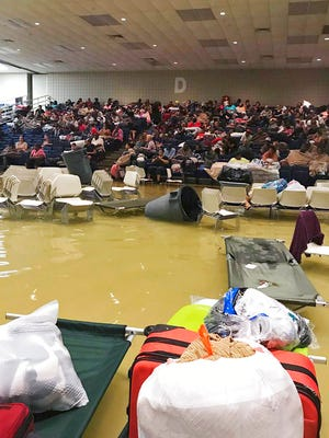 In this photo provided by Beulah Johnson, evacuees sit in the bleachers at the Bowers Civic Center in Port Arthur, Texas, Wednesday, Aug. 30, 2017, after floodwaters caused by Tropical Storm Harvey inundated the facility overnight. Authorities said it's not clear where the evacuees will go. (Beulah Johnson via AP)
