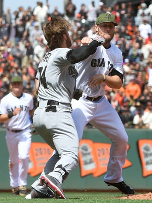 Bryce Harper and Hunter Strickland throw punches at one another after Strickland hit Harper with a pitch.