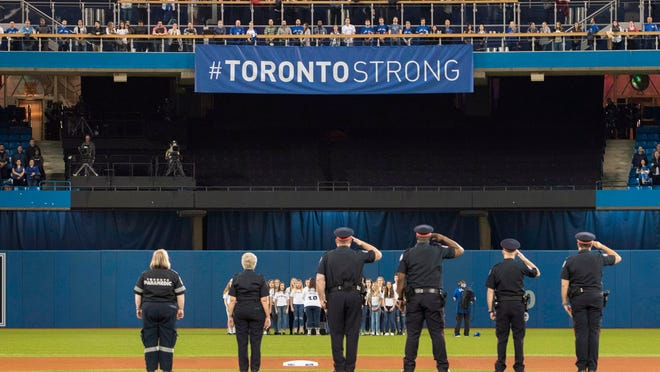 First responders who helped during Monday's deadly van rampage participate in the singing of the national anthem before a baseball game between the Boston Red Sox and the Toronto Blue Jays on Tuesday, April 24, 2018, in Toronto. (Fred Thornhill/The Canadian Press via AP)