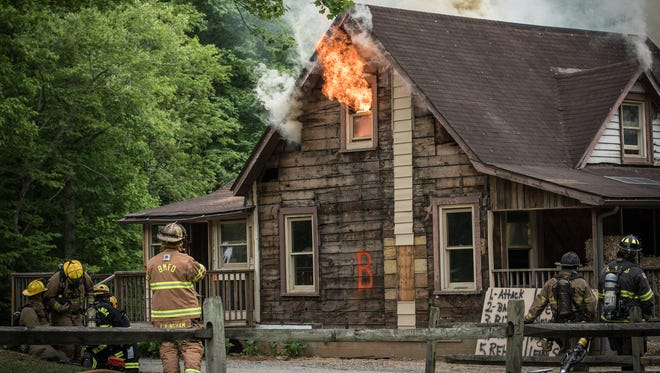 Local firefighters practice their skills while burning down an old house outside Montreat May 14.