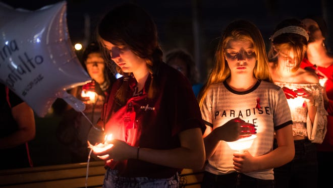 Nearly a hundred people attend a candlelight vigil at Memorial Park in downtown Stuart on Monday, Feb. 19, 2018, to honor the victims of last week's mass shooting at Marjorie Stoneman Douglas High School in Parkland. The vigil, which was organized by Florida PTA, was one of several held simultaneously across the state. People released balloons bearing the victims' names as they were read aloud.