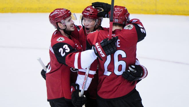 Arizona Coyotes defenseman Michael Stone (26) celebrates with right wing Shane Doan (19) and defenseman Oliver Ekman-Larsson (23) after scoring against the Minnesota Wild.