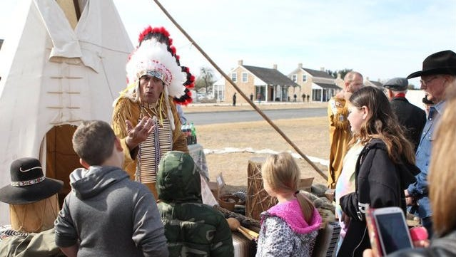 A crowd gathers around the Indian Lore tent as Chief Broken Eagle teaches them about Native American culture at the annual Christmas at Old Fort Concho in 2014.
