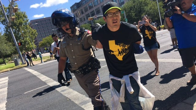 Manuel Ramirez, 25, right, was one of 15 protestors arrested in Austin Wednesday after they sat in traffic and blocked off streets. The activists were protesting Texas' role in challenging a federal rule protecting undocumented youth.