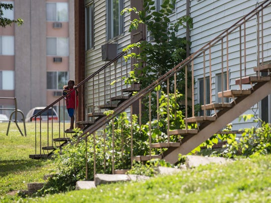 A child stands on the stairs outside of the River Hills