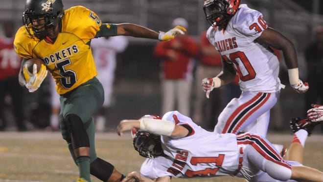 Rico Dowdle (5) breaks free from South Point tacklers during a 2013 game between the two schools.