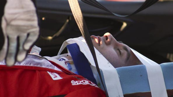 Matteo Malucelli, of Italy, is removed from his car after he was involved in a wreck during the IMSA Series Rolex 24 hour auto race at Daytona International Speedway in Daytona Beach, Fla., Saturday, Jan. 25, 2014.(AP Photo/Dow Graham)