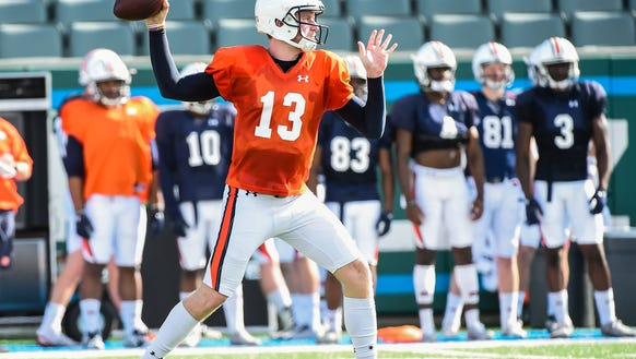 Auburn quarterback Sean White (13) throwing passes