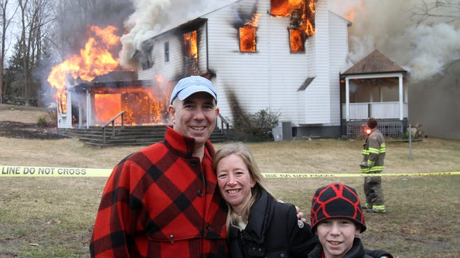 From left, Robert & Lynn Siegel along with their son Cody pose for a photo as their former Katonah home burns behind them March 29, 2014. The home was donated to the Katonah fire department for training purposes.