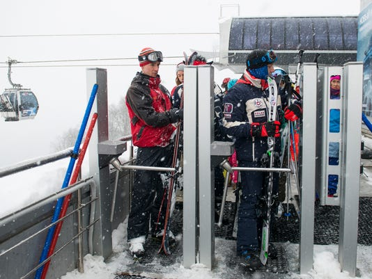 In this photo taken on Friday, Jan. 12, 2018, two visitors pass through the turnstile as they head to the piste at the Rosa Khutor ski resort in Sochi, which hosted Olympic skiing in 2014, Russia.The Russian government spent an estimated $51 billion on the Olympics and related infrastructure for Sochi, and the city's seeing the benefits. (AP Photo/Artur Lebedev)