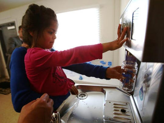 ": In this file photo, Alannie Rodriguez, 4, fills her water bottle from a new fountain with the help of her aunt, Gabriela Rodriguez. The ""tap"" at the San Jose Community and Bea Learning Center in Thermal is one of seven unveiled in January."