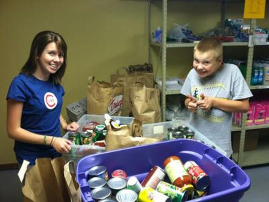 Peyton Medick, founder of Peyton's Promise, and her brother, Christian, show some of the food collected in a drive in this 2013 photos.