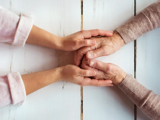 Younger woman's hands holding older woman's hands