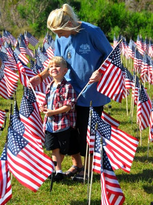 Robin Thomas and her grandson, Cash McIver, help set up 660 American flags last November at the Brevard Veterans Memorial Center on Merritt Island to raise awareness of PTSD-related suicides among troops and veterans.