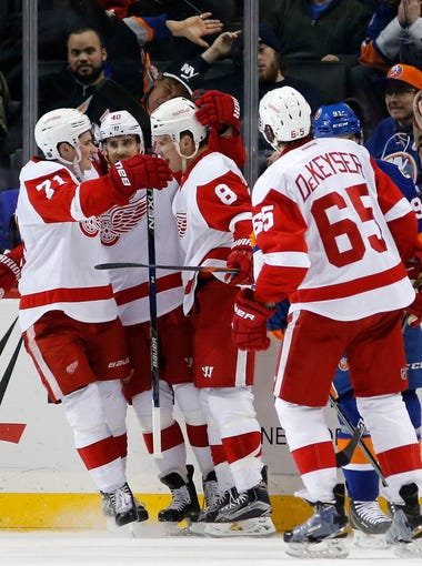 Detroit Red Wings center Dylan Larkin (71) and Red Wings left wing Henrik Zetterberg (40)  celebrate with  left wing Justin Abdelkader (8) after Abdelkader scored a goal against the New York Islanders as Red Wings' defenseman Danny DeKeyser (65) looks on in the second period of an NHL hockey game in New York, Monday, Jan. 25, 2016. The Red Wings won 4-2.