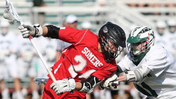 From left, Somers' Conor Jaykus (24) tries to drive on Yorktown's Thomas Cane (11) during first half playoff action at Yorktown High School May 23, 2018. Yorktown won the game 17-4.