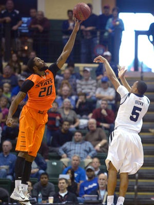 Oklahoma State's Michael Cobbins rises high to block a last-second shot by Butler guard Elijah Brown (5) to preserve a 69-67 victory.