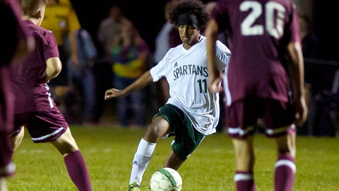 Winooski's Abbas Abdulaziz (11) dribbles past a BFA-Fairfax defender during Thursday night's boys soccer game in Winooski.
