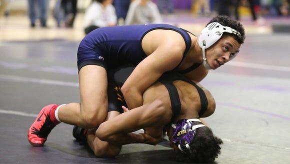 Putnam Valley's Kyle Sams wrestles Adrian Rosario from