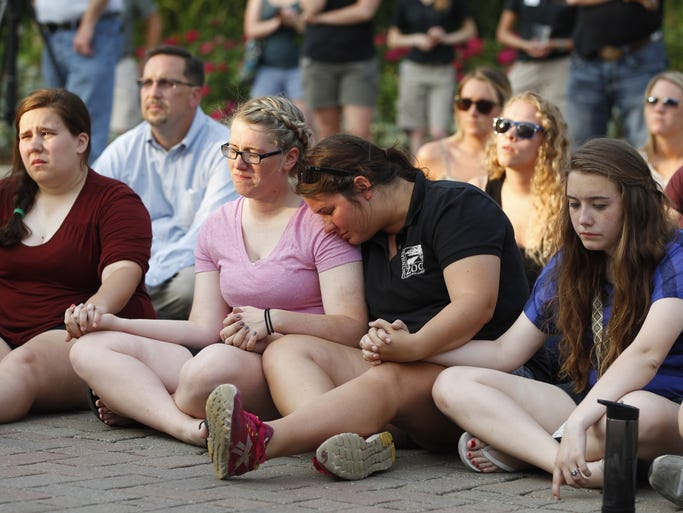 Friends, and former co-workers of Brogan Dulle console one another during a vigil held in his honor at the Cincinnati Zoo and Botanical Garden.