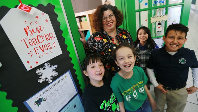St. Patrick School teacher Elizabeth Carreon stood with some of her students Wednesday. Carreon has been named Teacher of the Year and will be recognized Thursday at the SEED Awards ceremony.