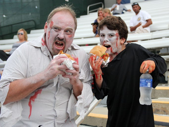 "Don and Brandon Lee of Fort Myers chow down on ""brain"" hamburgers during the Fort Myers Miracle ""Zombie Game"" Friday night at Hammond Stadium."