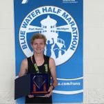 Tyler Champenoy poses with his Blue Water Half Marathon trophy