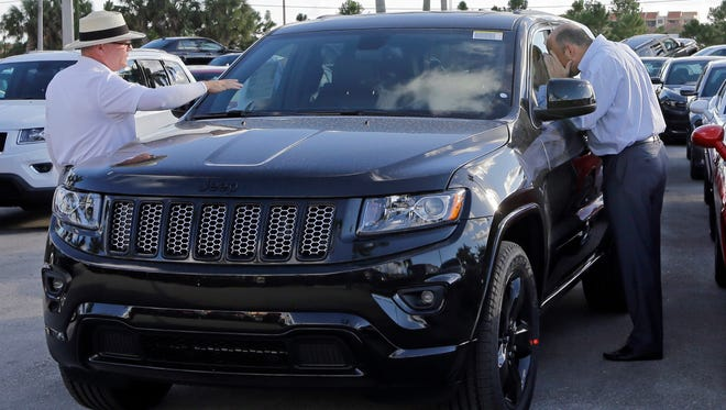 FILE - In this Thursday, Nov. 5, 2015, file photo, salesperson Andrew Montalvo, left, talks to a customer checking out the interior of a 2015 Grand Cherokee Limited in Doral, Fla. Fiat