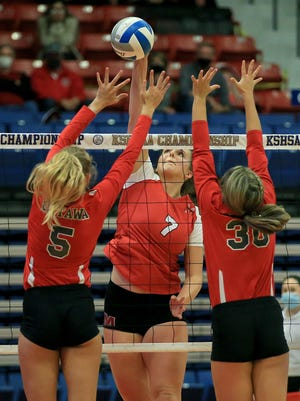 McPherson's Katie Berg (7) spikes the ball past Ottawa's Molly Olmsted (5) and Ella Keebaugh (30) in the Class 4A state volleyball tournament at the Sports Arena on Friday evening. Ottawa defeated McPherson 9-25, 25-12, 25-21, to place third in the tournament.