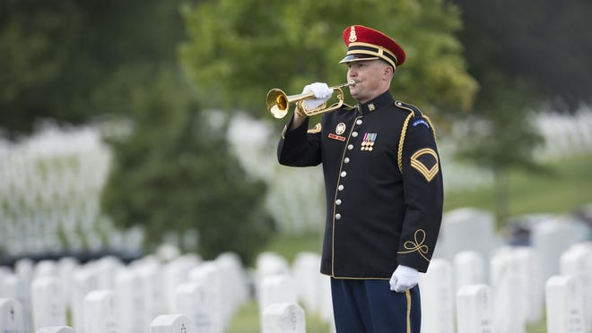 A bugler plays taps during funeral services for US Army Major General Harold Greene at Arlington National Cemetery in Arlington, Virginia, on August 14, 2014. Major General Greene was shot dead on August 5, 2014 at a training center in Kabul in an attack that left more than a dozen others wounded, including a senior German officer. He was the highest ranking US Army officer killed in combat since the Vietnam War. AFP PHOTO / Saul LOEB (Photo credit should read SAUL LOEB/AFP/Getty Images)