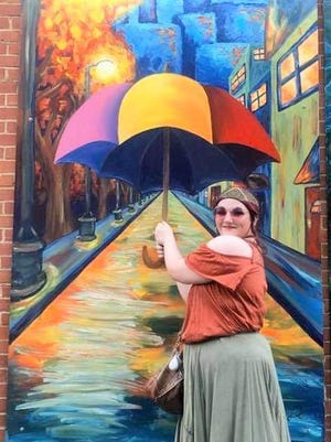 "Lauren Manon Gibson, a student at Southeastern Oklahoma State University, poses for a photo in front of ""Park West,"" a mural she painted, which hangs in downtown Durant as part of the Magnolia Mile Art Alley project. The piece won the top prize in a contest that was held June 5 to promote the project."